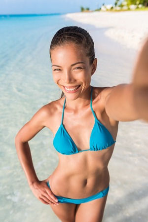 Summer vacation woman beach babe taking selfie of her beach body during travel holidays for Social Media. an. Happy mixed race Caucasian  Asian Chinese woman taking self portrait having fun.