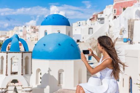 Europa reizen vrouw die foto fotograferen met behulp van slimme telefoon in Oia, Santorini, Griekenland. Beroemde blauwe koepels op een witte kerk in het dorp. Jonge Aziatische toerist die beelden op smartphone op feestdagen