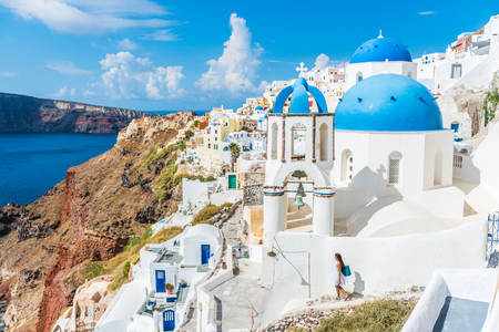 Europe, Greek Islands, Greece, Santorini travel tourist vacation destination: City of Oia. Woman on holidays walking on stairs visiting the famous white village by mediterranean sea and blue domes.