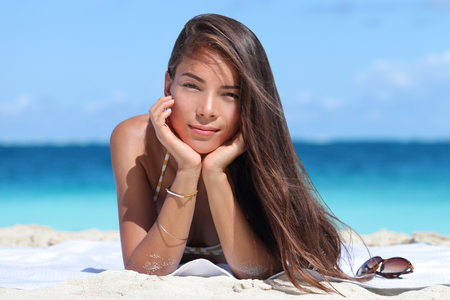 women hair: Beauty portrait of mixed race Asian Caucasian woman on beach. Young lady with perfect skin wearing bikini and jewelry - bracelet and necklace - relaxing on beach. Fashion model on vacation travel.