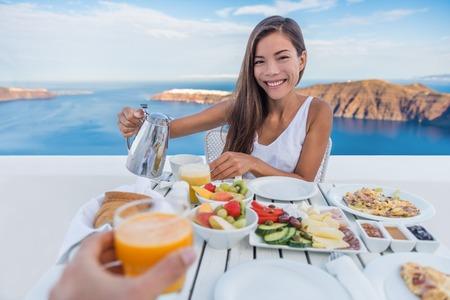 Paar eten ontbijt. Lachende toeristische vrouw drinken koffie en man drinken sinaasappelsap op het terras plaats buiten. Gezond en lekker eten geserveerd voor het ontbijt. Santorini, Griekenland.