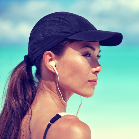 earbuds: Fitness runner woman listening to music on beach. Portrait of beautiful girl wearing earphones earbuds and running cap for sun protection. Asian woman healthy and active in summer. Stock Photo