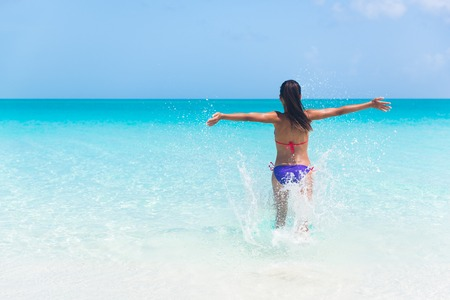exhilarated: Summer vacation woman happy running into ocean on beach splaching water cheering full of joy and excitement on holidays travel. Exhilarated girl tourist in bikini with arms outstretched cheerful. Stock Photo