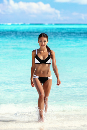 Sexy bikini woman on beach coming out of water walking relaxing on tropical getaway paradise. Young Asian ethnic model with slim weight loss body sunbathing in summer vacation travel. Stock Photo
