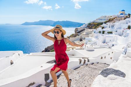 caminando: El viaje turístico de la mujer feliz que se ejecuta Escaleras de Santorini, Islas Griegas, Grecia, Europa. Chica de vacaciones de verano visitando famoso destino turístico que tiene sonrisa de la diversión en Oia. Foto de archivo