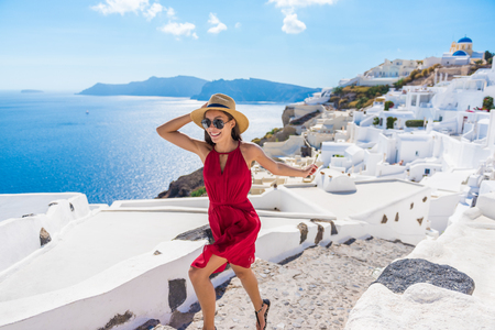greece: Travel Tourist Happy Woman Running Stairs Santorini, Greek Islands, Greece, Europe. Girl on summer vacation visiting famous tourist destination having fun smiling in Oia.