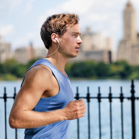 escucha activa: hombre joven urbano que se ejecuta en parque de la ciudad escucha la m�sica con Bluetooth inal�mbrico auriculares de bot�n que viven un estilo de vida saludable y activo. Corredor masculino superior azul que se resuelve el entrenamiento de ejercicio cardiovascular en verano. Foto de archivo