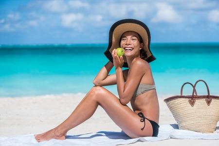 dieta sana: Mujer asiática que come sano el viaje de vacaciones de playa en morder la manzana fresca como una dieta de pérdida de peso para un cuerpo de bikini. Turista de la niña feliz que disfruta de la comida vegetariana orgánica se relaja en vacaciones de verano.