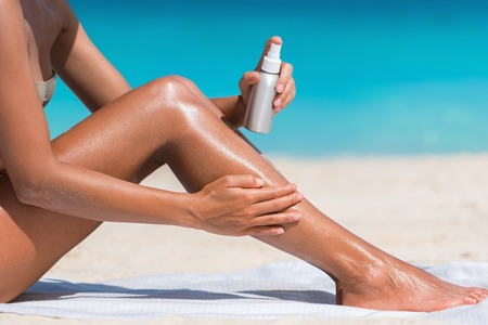 Sunscreen suntan lotion in spray bottle. Young woman in spraying tanning oil on her leg from bottle. Lady is massaging sunscreen lotion while sunbathing at beach. Female model during summer vacation. Stock Photo