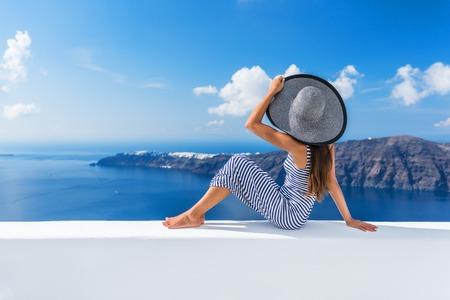 지중해 바다와 산토리니 이아 (Oia)의보기를 찾고 야외 테라스에서 휴식 유럽 여름 휴가 여행 크루즈 목적지 고급 생활 여자. 패션 비치웨어 우아한 관 스톡 콘텐츠