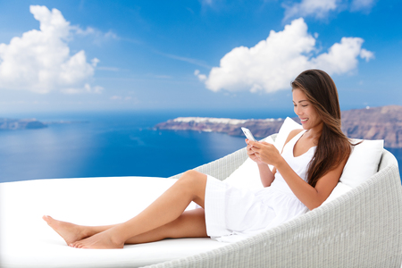 daybed: Asian woman using phone app relaxing on daybed on outdoor terrace. Home living outside patio furniture. Young adult texting on smartphone lying on sofa with Oia Santorini background enjoying summer. Stock Photo
