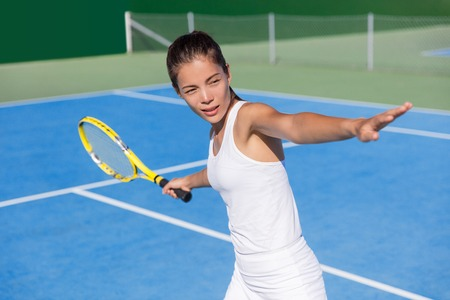 forehand: Asian tennis player woman playing hitting forehand in white dress outfit on blue hard court outdoor in summer holding racket. Female athlete determination and concentration concept.
