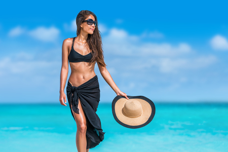 Elegant beach woman in bikini and fashion sarong standing on shore. Sexy lady in black beachwear, floppy hat, sunglasses enjoying sun on tropical destination during summer vacation in the Caribbean. Imagens