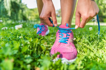 lacing sneakers: Healthy active lifestyle woman athlete tying running shoes. Happy sporty runner girl lacing shoelaces on pink fashion sneakers on summer grass in city park getting ready for a fitness morning jog.
