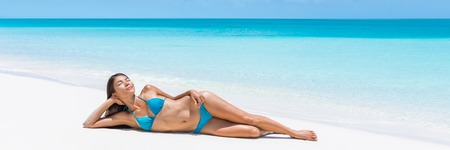 lying on back: Caribbean turquoise ocean getaway beach destination lady dreaming on perfect white sand. Paradise tropical travel destination. Asian blue bikini woman lying down relaxing sun tanning laid back. Stock Photo