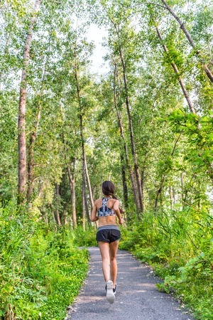 activewear: Runner woman training cardio running on forest path in city park in summer nature. Back of girl jogging living a healthy active lifestyle wearing sports activewear clothing working out full length.