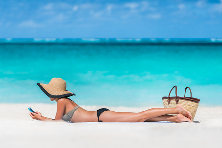 sunny beach: Beach vacation girl using mobile phone app texting sms or sharing photos on social media during summer travel holiday. Bikini woman relaxing sunbathing on sand lying on towel wearing sun hat. Stock Photo
