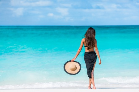 Woman in black bikini and sarong standing on beach. Elegant female is wearing black bikini and sarong on beach. Woman is holding sunhat enjoying her summer vacation at resort in the Caribbean.