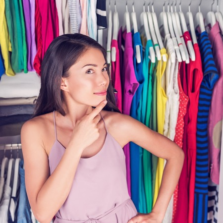 changing clothes: Home closet or store clothing rack changing room. Woman choosing her fashion outfit. Shopping girl thinking what dress to wear to go on a date. New trendy colorful clothes in organized clean walk-in. Stock Photo