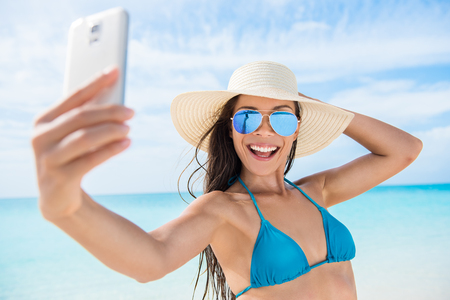 mirrored: Selfie smartphone girl taking mobile phone photo on beach vacation during summer travel holidays. Sexy young bikini woman wearing fashion mirrored aviator sunglasses posing for camera having fun.