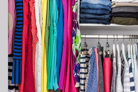 Fashion clothes in walk-in clothing closet or store display for shopping display. Colorful choices of trendy outfits well arranged in clean racks. Spring cleaning concept. Summer home living wardrobe. Stock Photo - 56700651