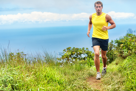 healthy path: Running man runner living a healthy life active lifestyle. Male young athlete training cardio working out legs on a trail path in forest nature park and green grass in mountains with ocean background. Stock Photo