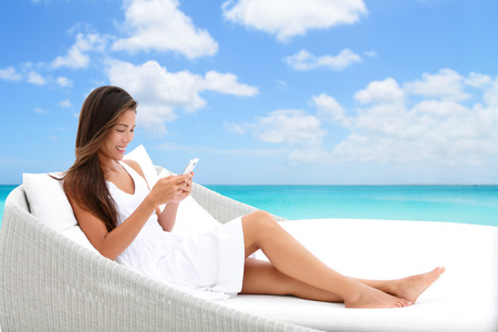 Woman using phone app relaxing on sun bed on outdoor terrace. Home living outside patio furniture Asian girl on smartphone lying on beach lounger in white dress with ocean background enjoying summer.