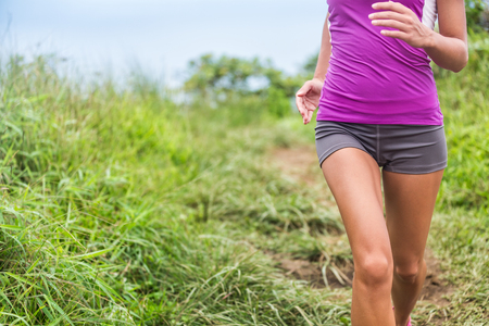 menstrual pain: Healthy active woman runner running in outdoor grass nature park trail path. Midsection lower body of girl athlete training cardio. Feminine health care issues: menstrual period pain, stomach problem. Stock Photo