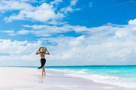 Luxury travel woman in black beachwear sarong walking taking a stroll on perfect white sand Caribbean beach. Girl tourist on summer holiday holding sun hat at vacation resort. Tropical landscape. Banque d'images