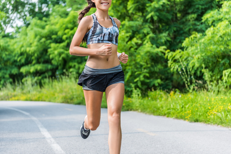activewear: Fitness girl running in summer outdoor park. Happy fit athlete working out in sports bra and 2-in-1 compression shorts fashion activewear outfit showing off slim body and abs training for weight loss. Stock Photo