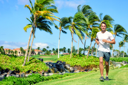 residential neighborhood: Active lifestyle man runner jogging in high end luxury residential american tropical neighborhood - Miami Florida living. Healthy running male fitness athlete working out cardio on grass in summer.