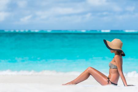 비키니 여자 해변 휴가 태양 선탠 해변에서 휴식. 선탠 개념입니다. 카리브해 휴가 열 대 태양 아래 일광욕 모자 밀 짚 모자와 햇빛을 즐기는 인식 할