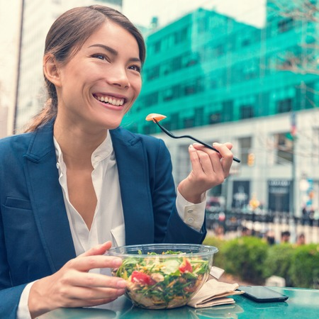 Asian business woman eating healthy salad vegetarian takeaway cafe meal at work during lunch break on outdoor terrace city park in summer. Happy businesswoman having a balanced diet for weight loss. Stock Photo