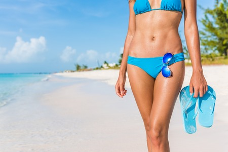 Sexy bikini body woman - abs, sunglasses, flip flops on beach vacation. Model showing slim abs and tanned skin on tropical caribbean travel destination vacation. Belly button stomach and thighs legs. Stockfoto