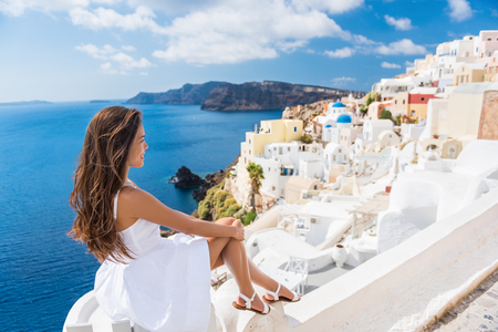 Europe summer travel destination Santorini tourist woman on vacation relaxing. Asian girl in white dress visiting the streets of the famous white village Oia with the mediterranean sea and blue domes.