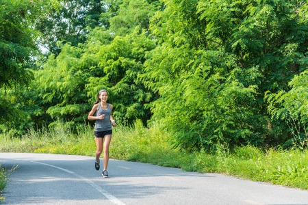 healthy path: Running girl runner jogging on nature park path during summer training cardio for marathon race or weight loss goal success. Athlete Asian woman with fit body living a happy healthy lifestyle.