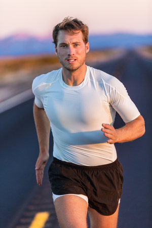 activewear: Athlete endurance runner man long distance running with focus and determination on desert road at sunset. Sportsman training in compression sports t-shirt and shorts activewear in summer landscape.