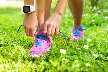 sport shoe: Active lifestyle smartwatch runner woman tying running shoes. Healthy summer living. Sports girl getting ready for weight loss run exercise lacing footwear laces wearing activity tracker wristwatch. Stock Photo