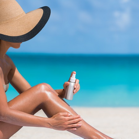 Beach body suntan skin care travel vacation. Bikini hat woman applying sunscreen lotion putting cream on tanned sexy legs sunbathing sun tanning sitting on sand with turquoise blue ocean background.