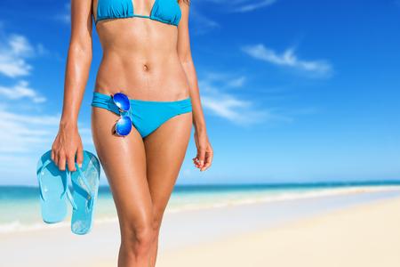 섹시 한 해변 비키니 아름 다운 여자 비치 샌들과 선글라스 필수 액세서리를 들고 열 대 휴가에 일광욕을 편안 하 게. 복부 복근과 다리 작물. 썬탠 스