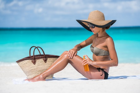 Beach accessories essentials for a summer holiday tropical vacation: sunglasses, straw hat, tote bag, towel, sunscreen. Sexy bikini woman applying sunblock sun protection lotion on Caribbean travel.