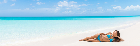 paradise beach: Paradise tropical vacation woman relaxing on perfect white sand beach Caribbean travel destination. Luxury living dreamy getaway Asian skincare model lying down sun tanning in secluded resort.