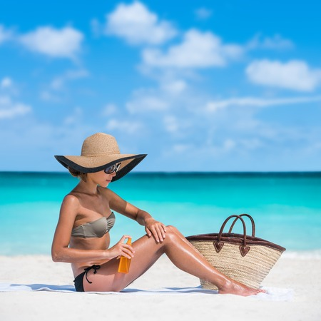 Sun protection uv rays skincare. Sunscreen spray bottle woman applying body lotion on smooth legs. Girl tanning putting sunblock Beach essentials for summer holidays: straw hat, sunglasses, tote bag.