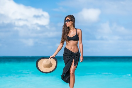 Elegant beach woman in bikini and fashion sarong standing on shore. Sexy lady in black beachwear, floppy hat, sunglasses enjoying sun on tropical destination during summer vacation in the Caribbean. Фото со стока