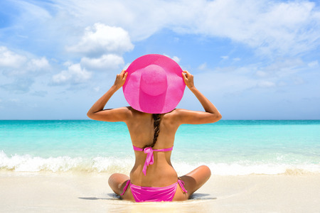 Cute pink bikini beachwear woman relaxing in perfect paradise destination on beach travel vacation. Girl from the back holding fashion straw floppy hat sitting on sand looking a turquoise ocean.