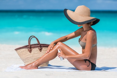 Girl oil spray tanning her legs protection from the suns uv rays putting sunscreen lotion sunblock Unrecognizable girl with her beach essentials for a summer holiday - straw sun hat and tote bag.