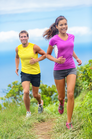 healthy path: Healthy couple athletes trail running in outdoor nature path. Happy young adults training together during summer in mountains or grass park. Multi-ethnic group, Asian woman with Caucasian man trainer.