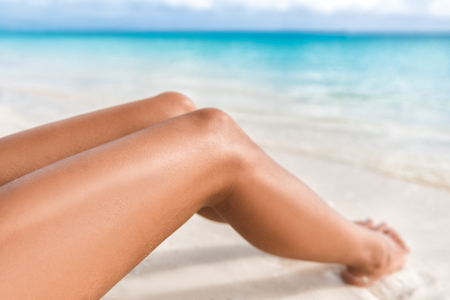 Sexy suntan bikini woman legs relaxing lying down on white sand beach summer vacation. Beauty skincare sun aging protection body care of tanned skin. Epilation laser or shaving concept. Stock Photo