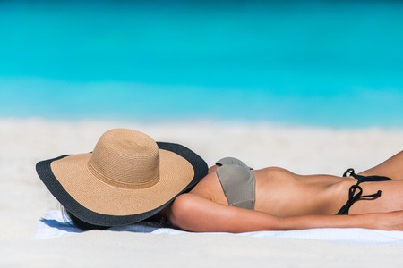 sun tanning: Beach relaxation woman sleeping sun tanning covering her face with straw hat for uv solar protection on caribbean destination blue ocean background. Vacation girl relaxing resting on summer travel. Stock Photo