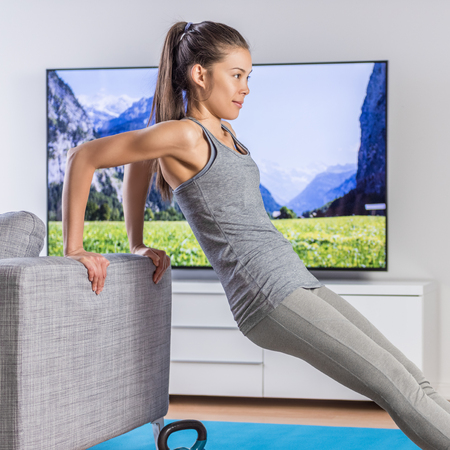 Training at home without weights or any gym equipment! Young Asian fit woman exercising her triceps with bodyweight exercises on living room sofa working out arms watching tv fitness video workout.